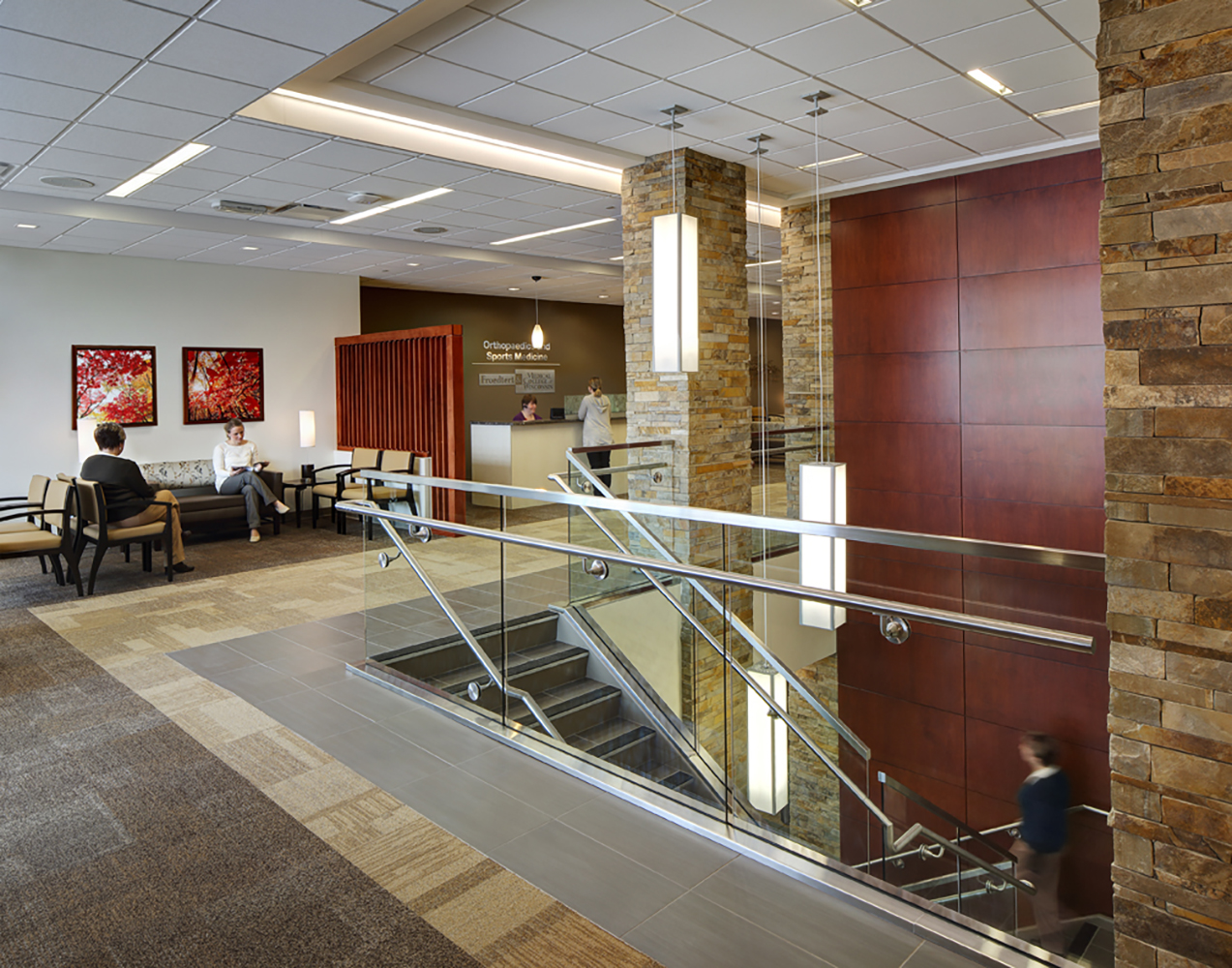 Parallel pendants in a hospital lighting application above a modern open stairwell near a cozy waiting area.