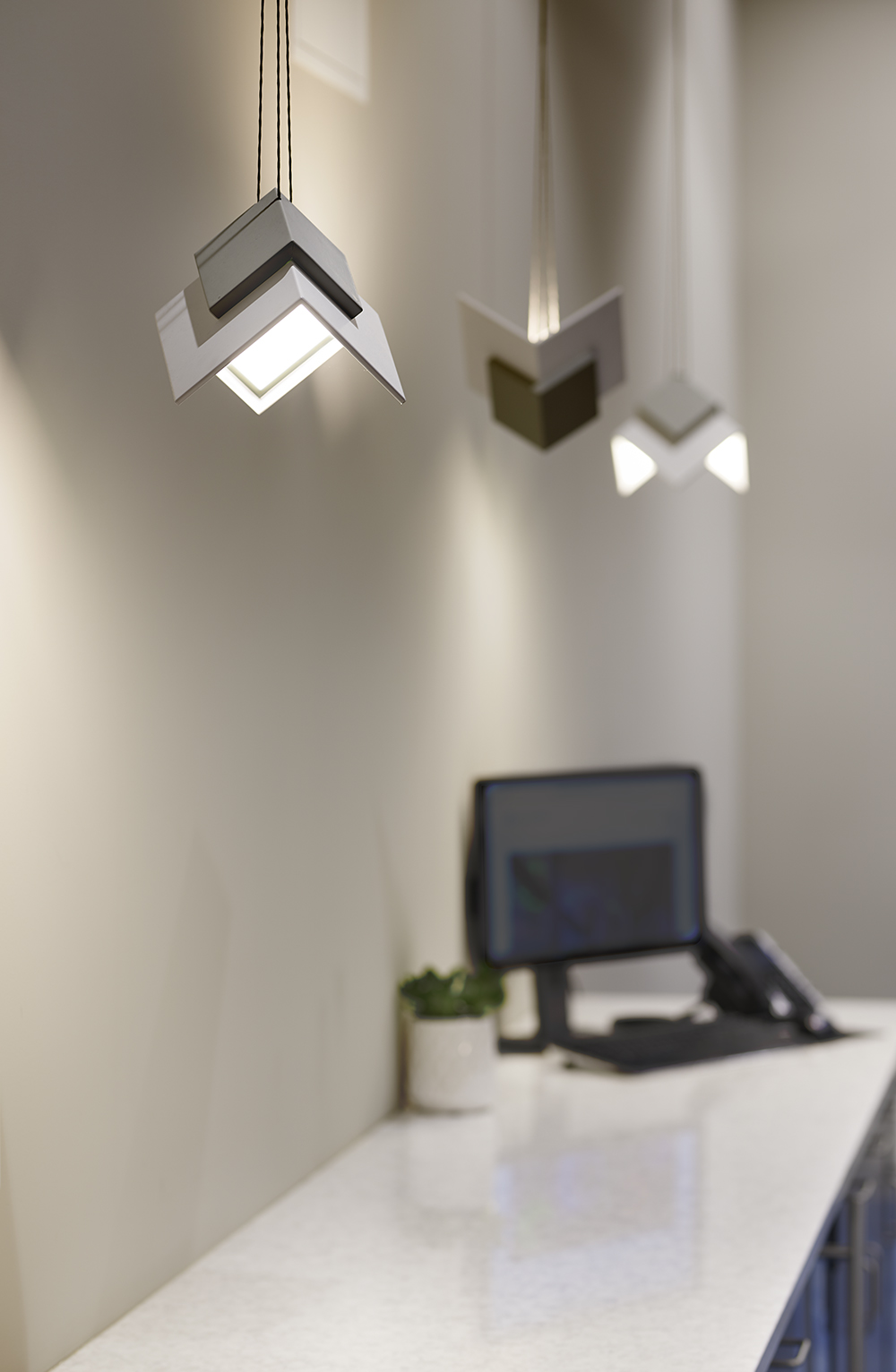 Petal OLED pendants as office lighting fixtures along a meeting room wall.