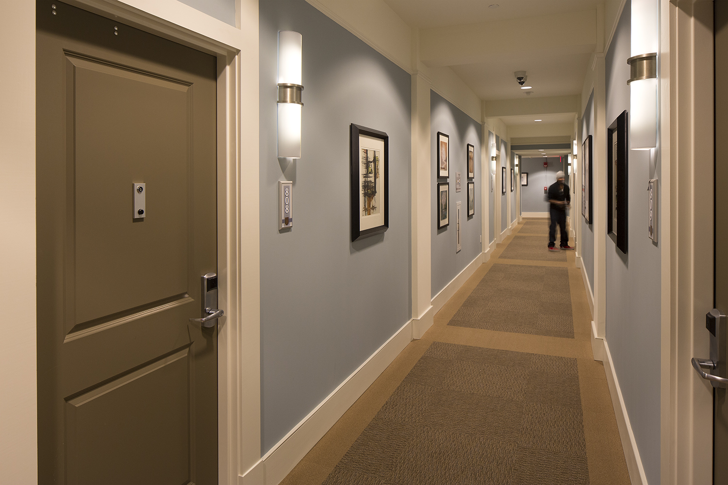 Pila sconces are ideal for hotel or apartment lighting applications, seen here alongside doors in a residential hallway.