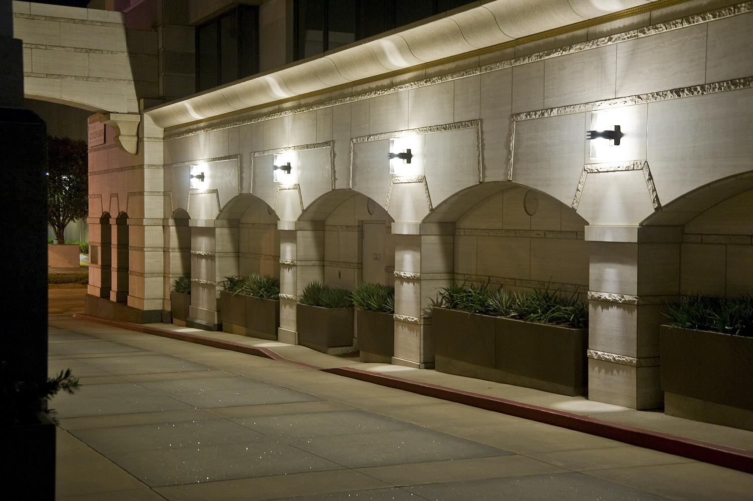 Pla outdoor light fixtures provide uplight and downlight on a classic arch structure along a city street at night.