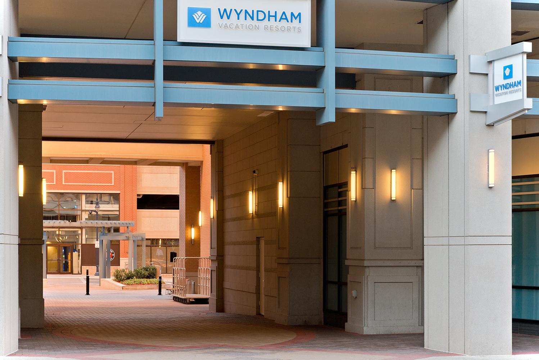 Raven exterior lighting fixtures along an exterior passageway between buildings in an outdoor commercial area.