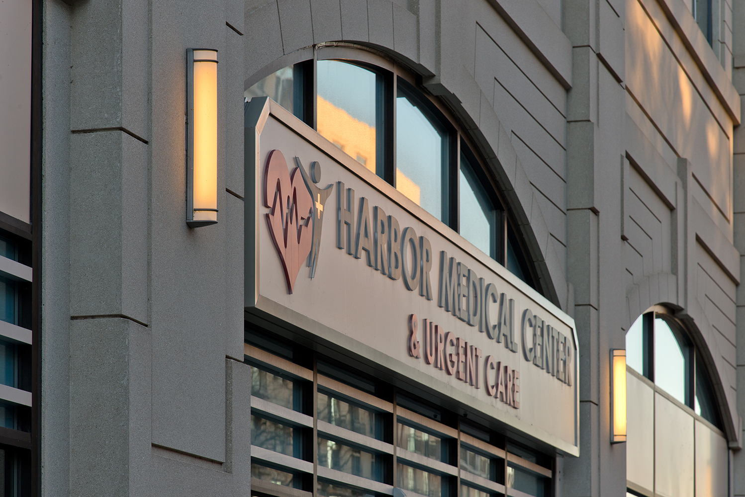 Raven outdoor light fixtures along a large medical center sign, mounted vertically.