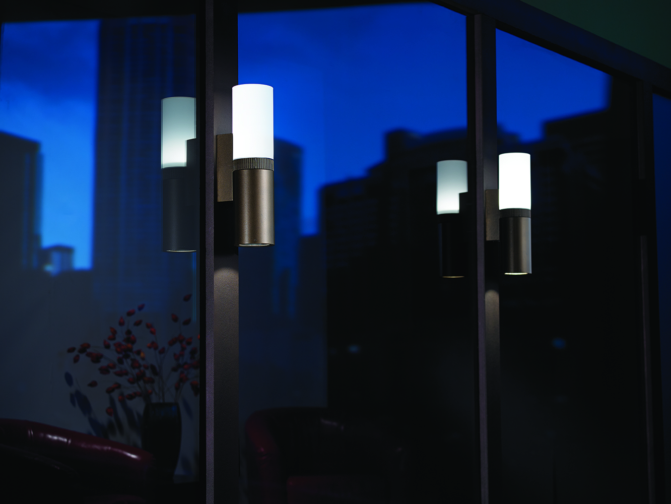 Scope exterior lighting fixtures illuminate large windows at night, reflecting a city skyline.