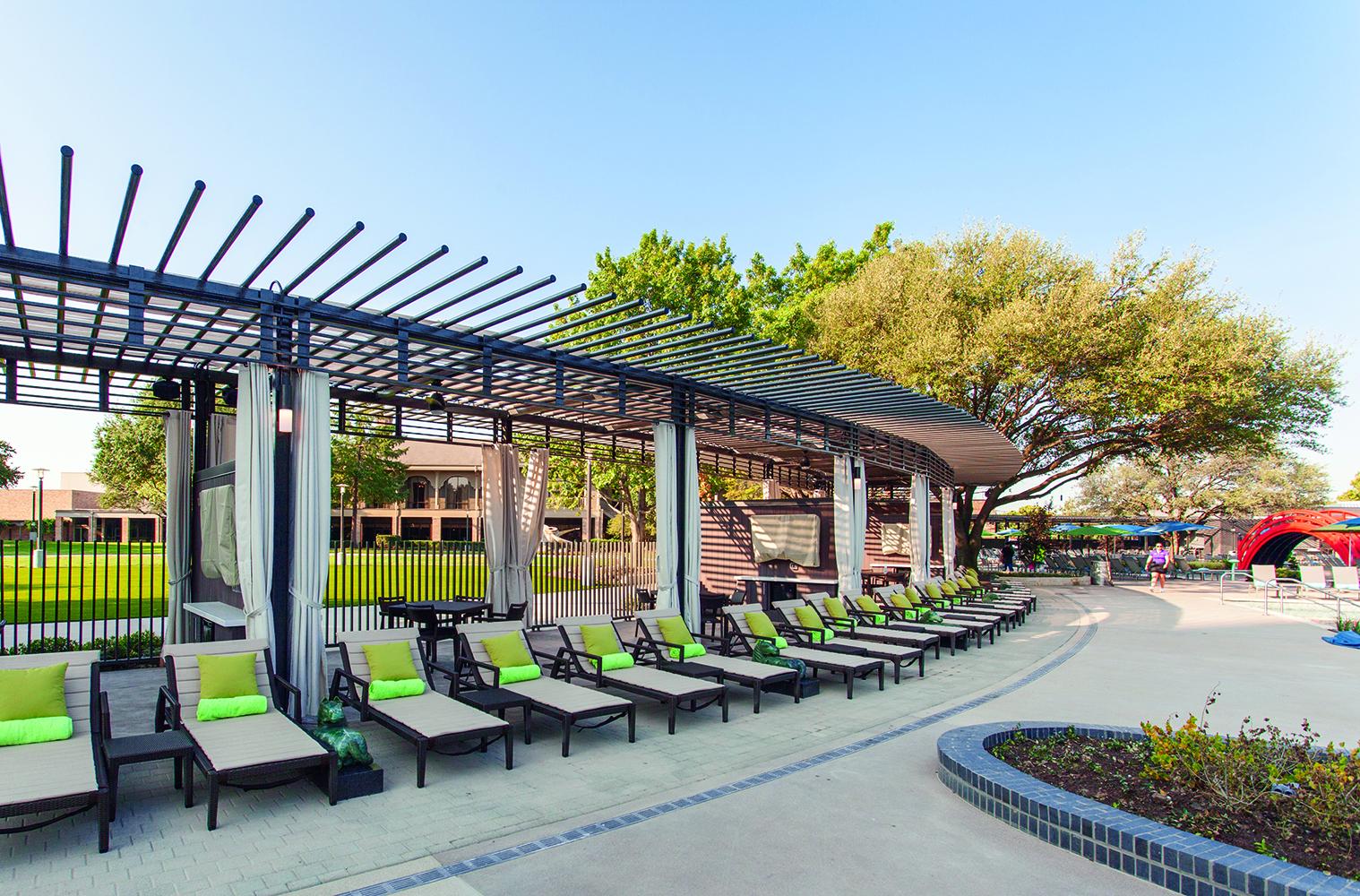 Scope modern lighting fixtures illuminate a poolside pergola structure.