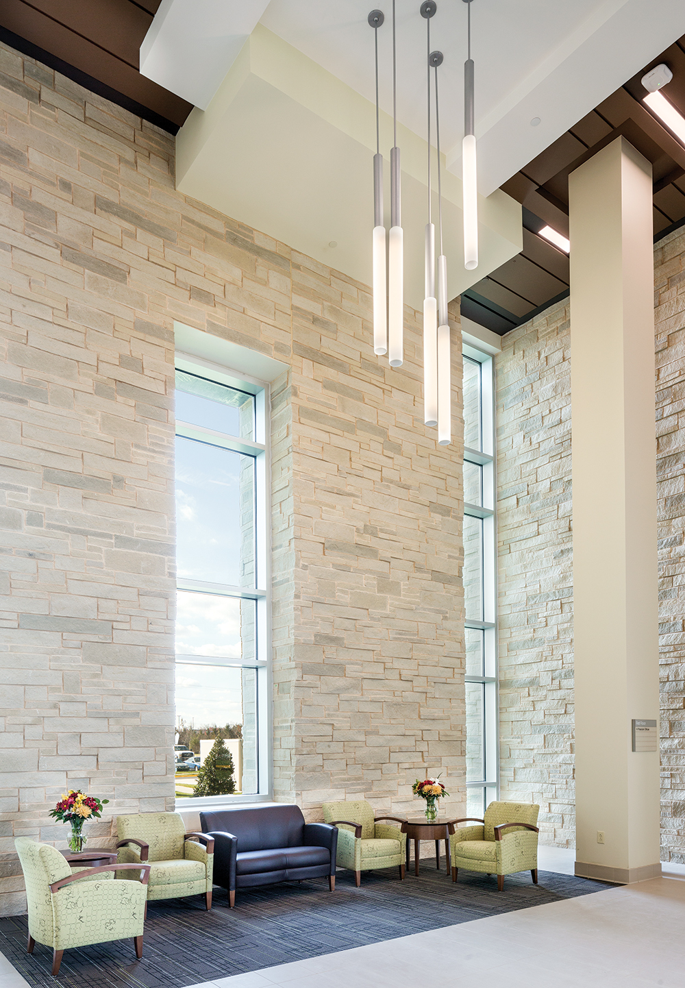 Sequence pendants highlight a clean, comforting healthcare design in a large waiting area with stone walls and green furniture.