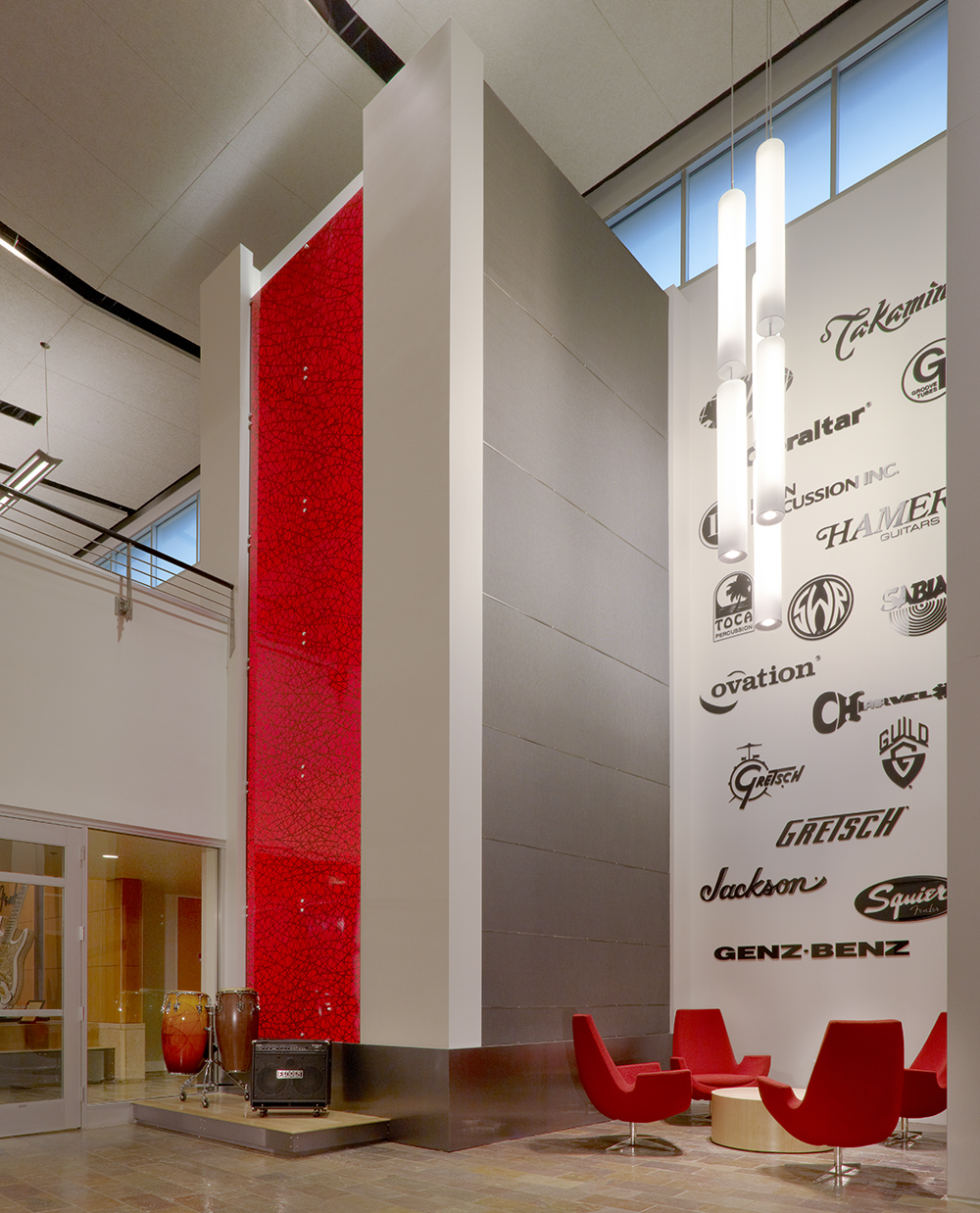 Sequence pendants provide eye-catching illumination in a large light fixture configuration for a high-ceiling lobby above red chairs.