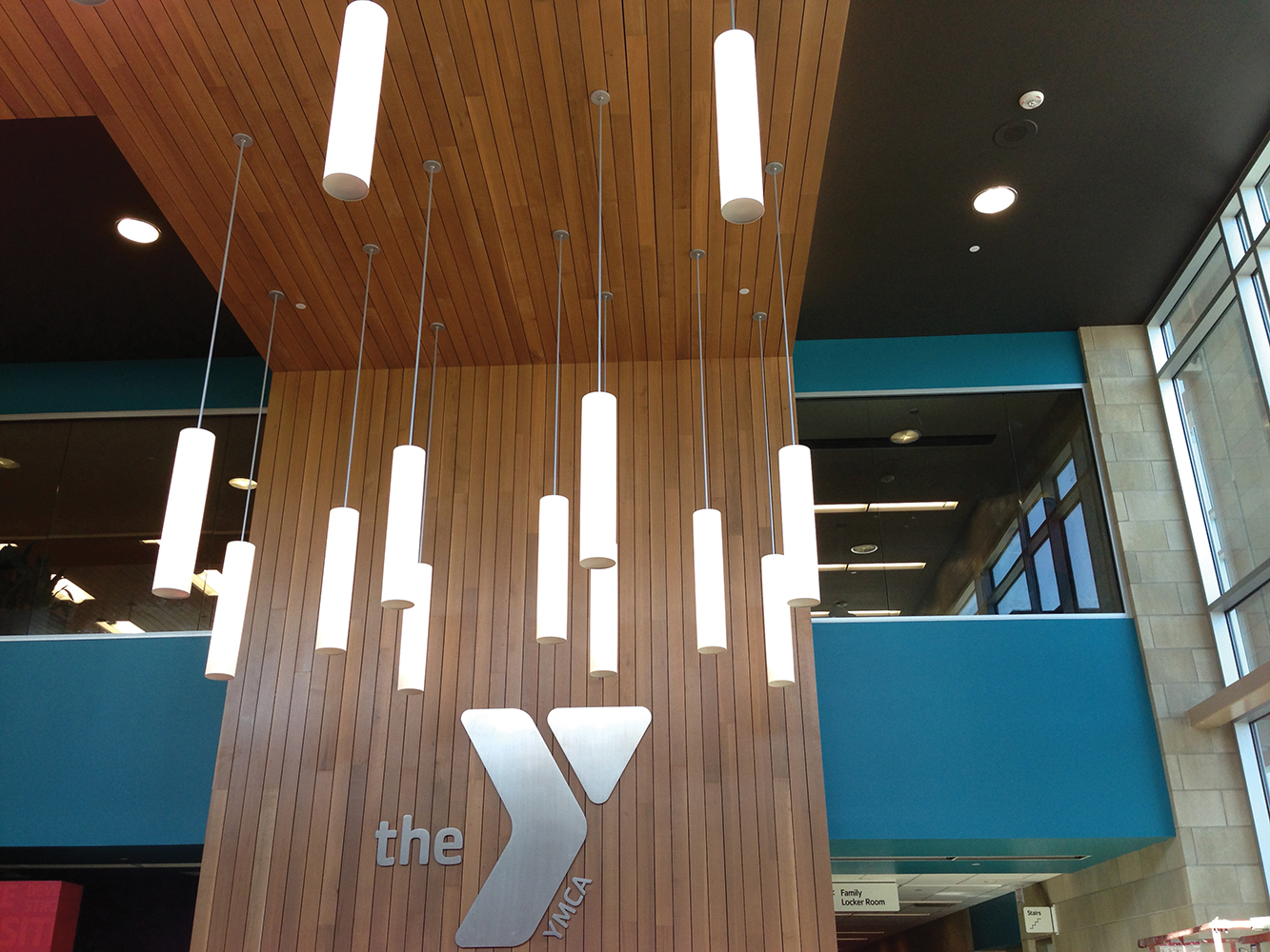 Sequence modern lighting fixtures illuminate a wood-paneled YMCA entryway.