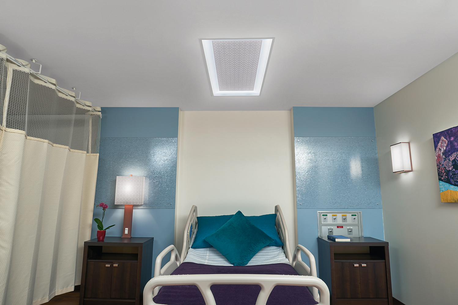 Serenity patient room lighting fixtures illuminate a hospital bed from a table lamp, overbed luminaire, and wall sconce.