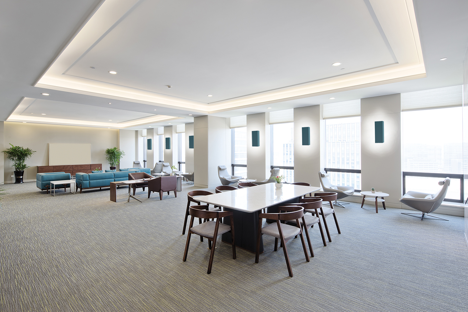 Shield sconces provide attractive indirect light in a large meeting room area for relaxing office lighting design.