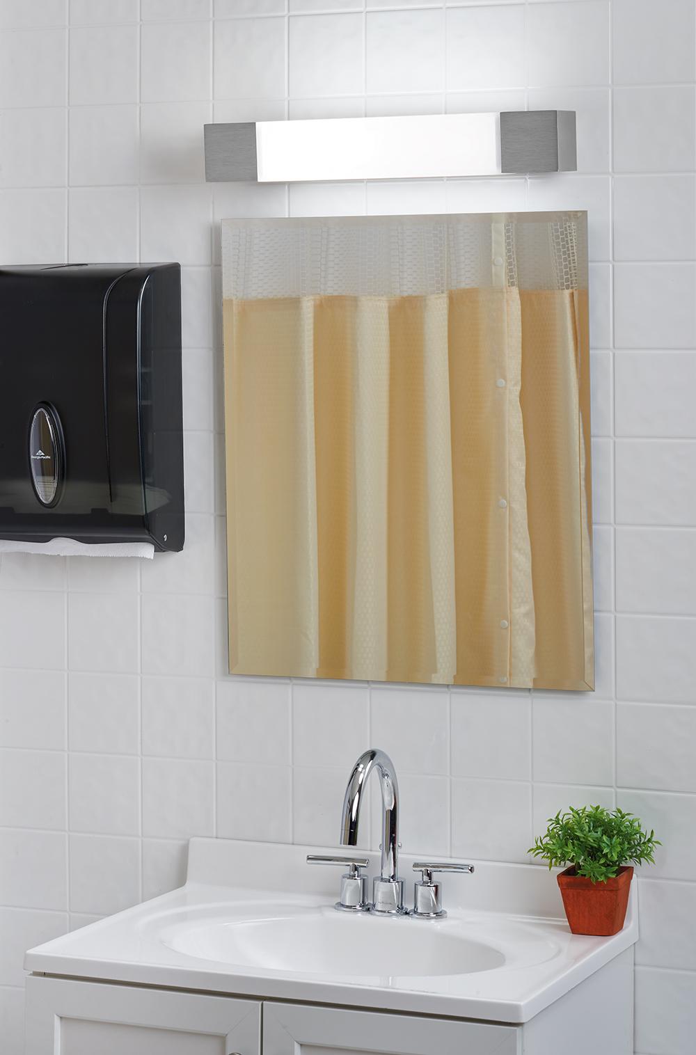 Shine modern vanity light fixture mounted horizontally over a minimalist mirror and vanity for modern apartment lighting design.
