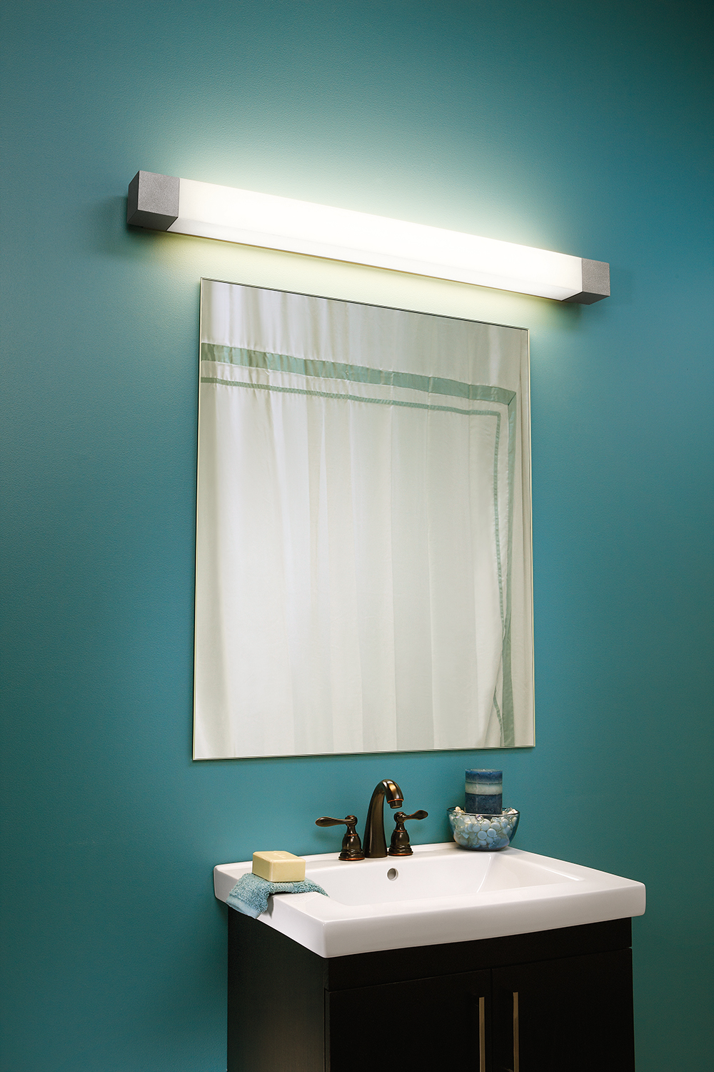 Shine modern vanity light fixture mounted horizontally over a minimalist mirror and vanity for multifamily residential design.