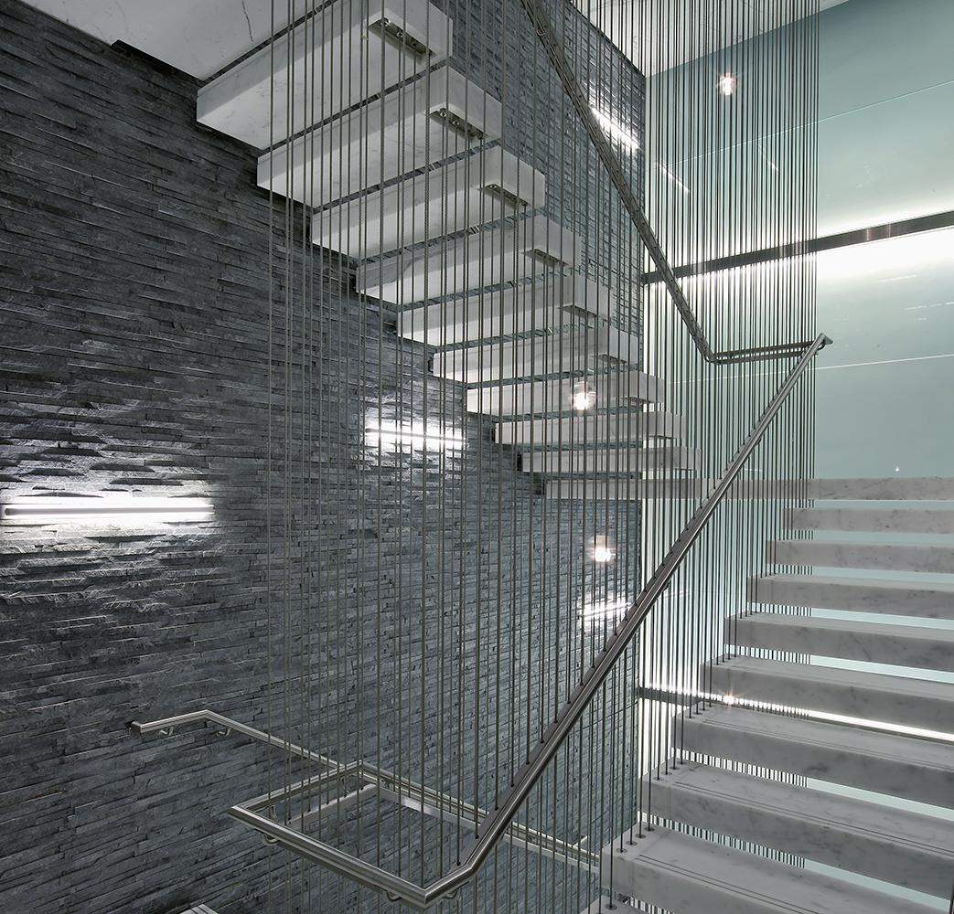 Sleight office lighting illuminating an ultra-modern textured stairwell wall.