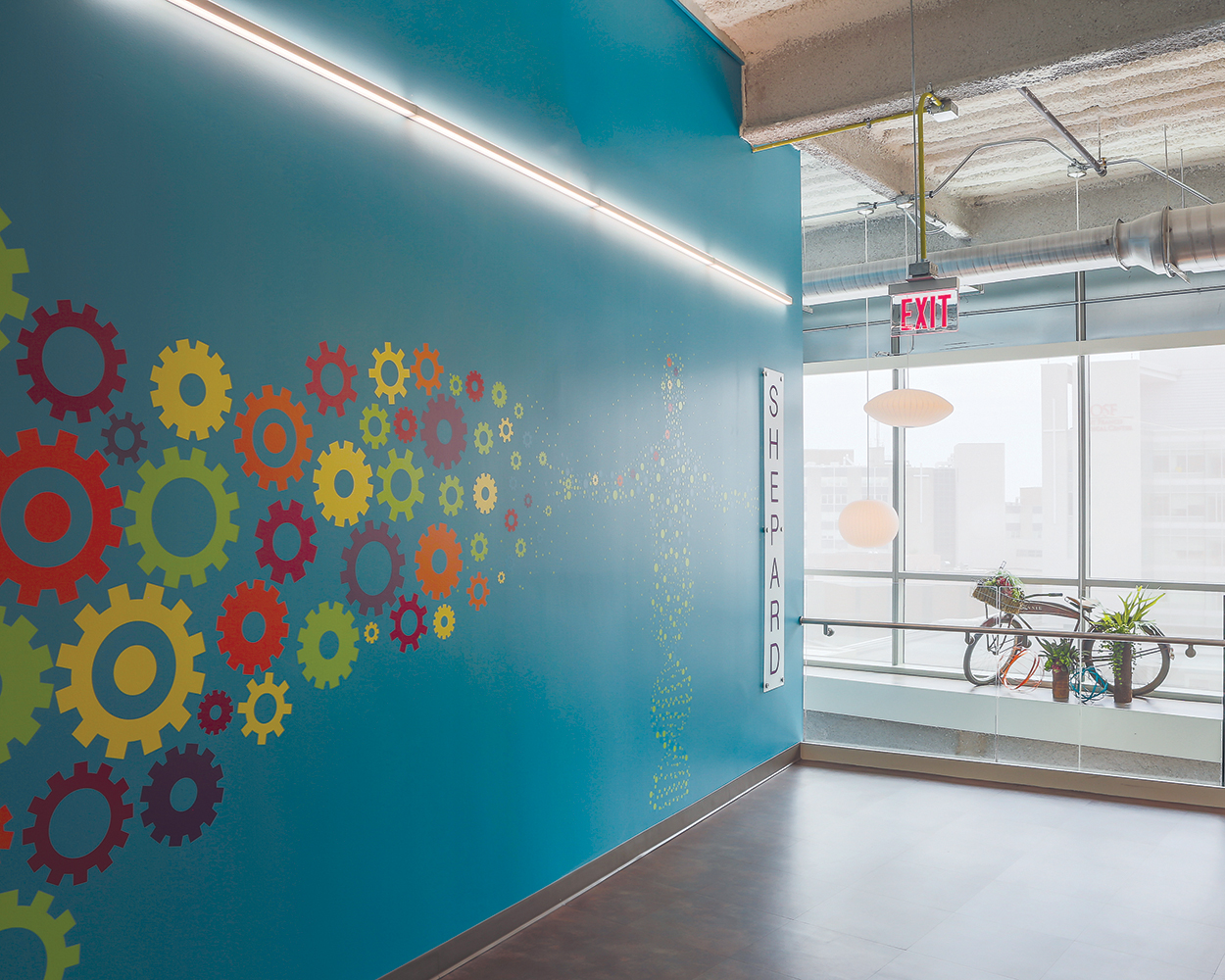 Sleight illuminates a blue wall with colorful gear icons for a modern office lighting design.