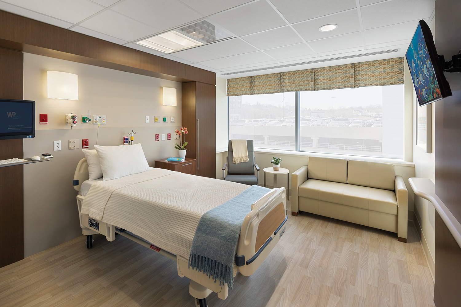 Unity overbed and wall sconce luminaires provide comforting medical lighting in a bright patient room.