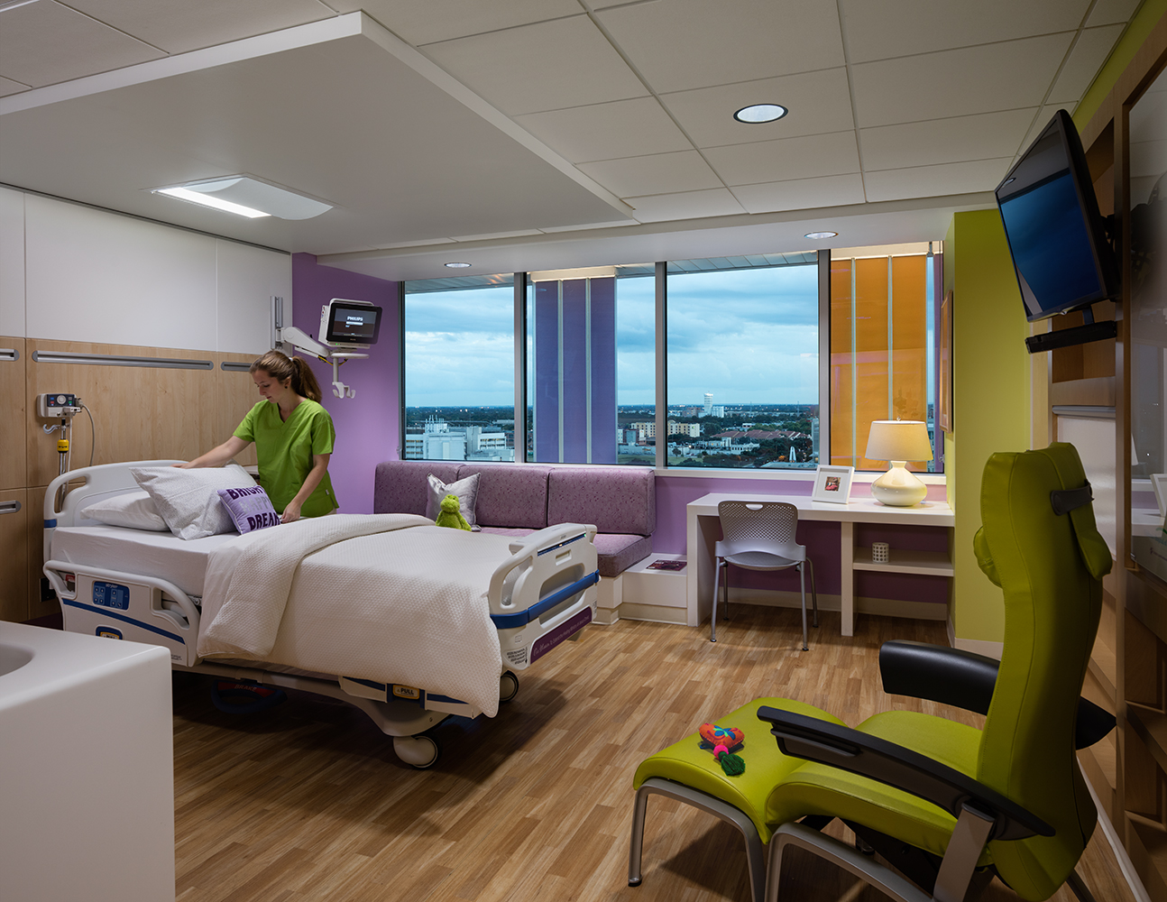 Unity overbed luminaire provides patient room lighting while a nurse adjusts the bedding.
