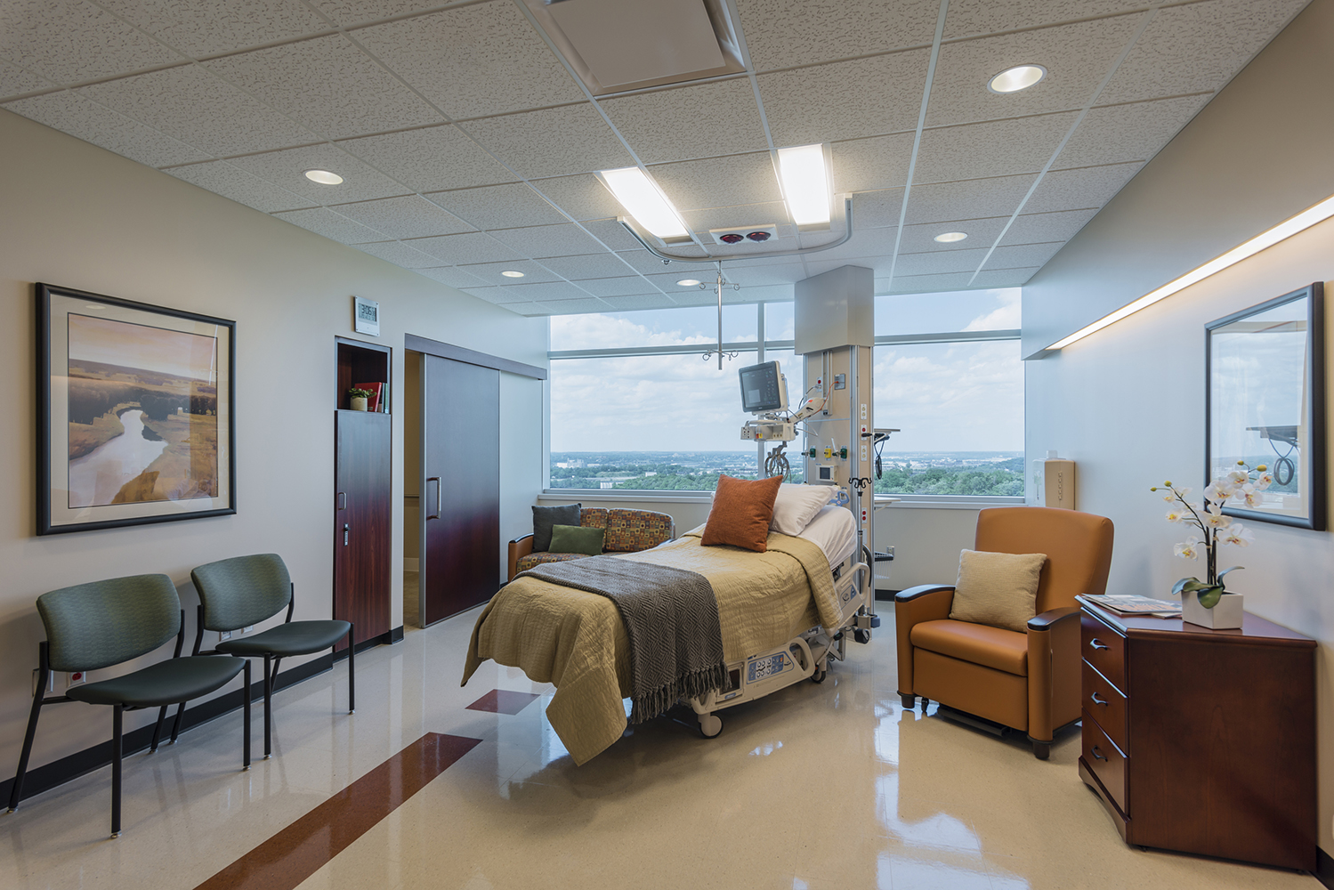 Unity patient room lighting over a patient bed in front of a wide window.