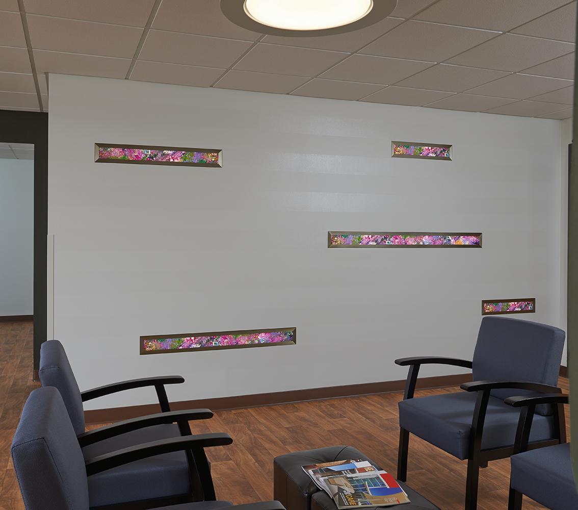 Visage medical lighting, featuring Vara Kamin artwork, illuminates the bed in a small exam room.