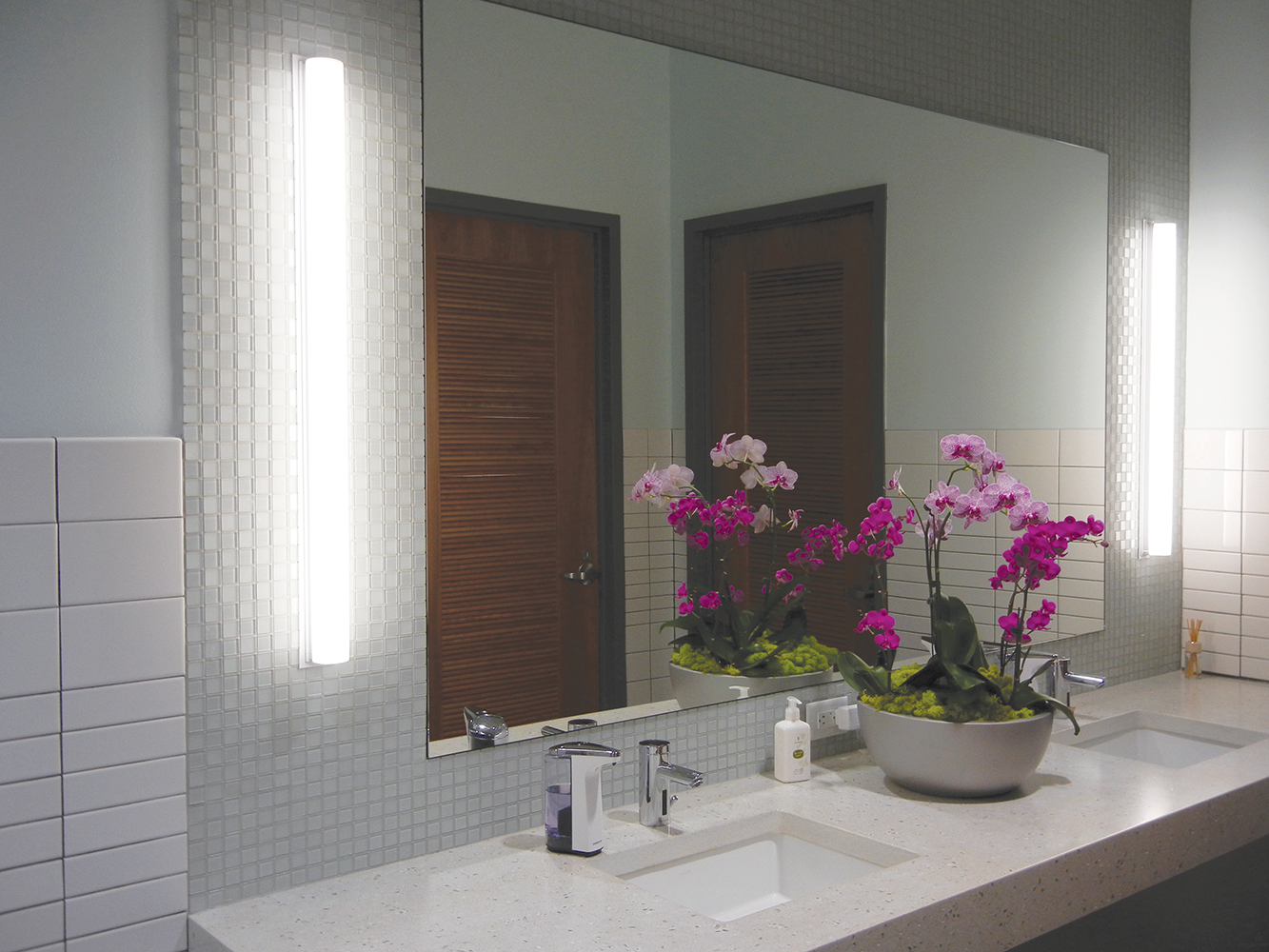 Voila modern vanity light fixtures illuminate mirrors in sleek, clean restroom with a bowl of purple flowers between two sinks.