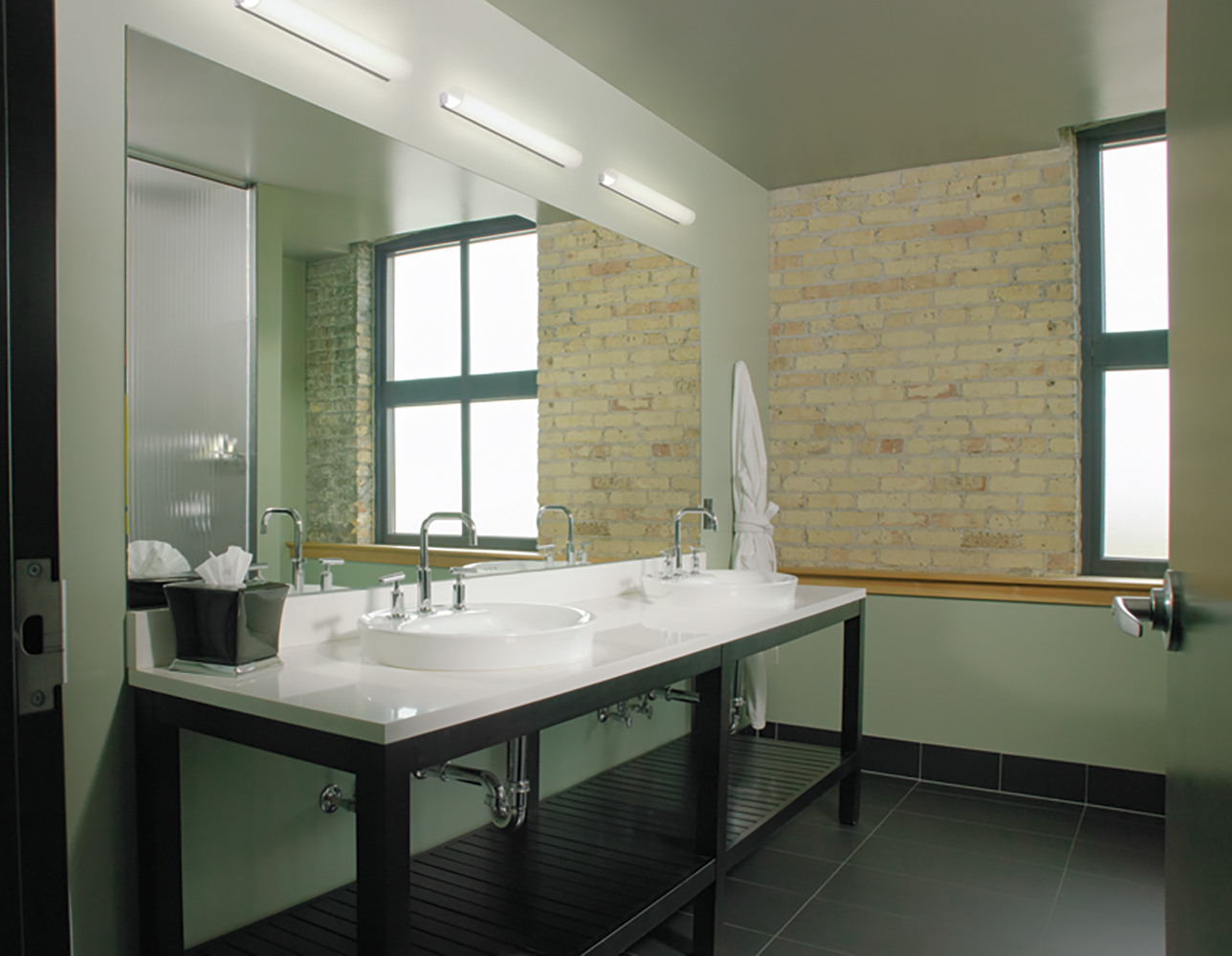 The Voila modern vanity light fixture, a luminous linear tube, above a clean mirror and double sink in a small bathroom.