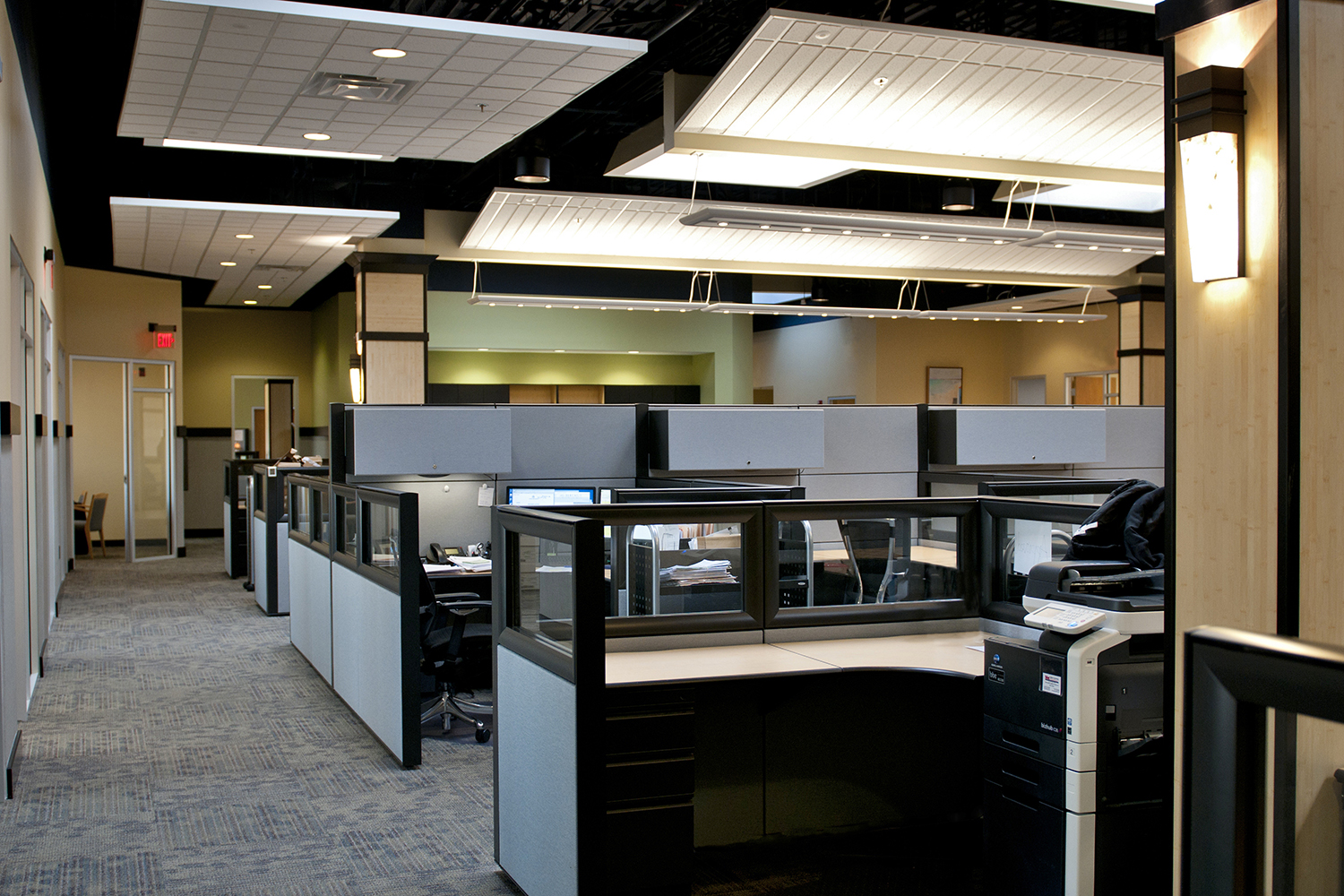 Wedge sconces illuminate a modern office lighting design, shown along the wall of an open cubicle area with an exposed ceiling.