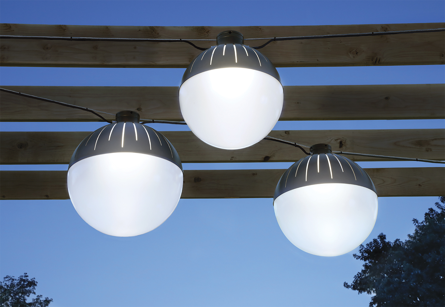 Zume outdoor light fixtures illuminate a wooden pergola structure below a darkening night sky and tall trees.