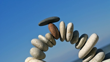 Rocks at a beach balanced in an arch shape illustrating the delicate nature of behavioral health design