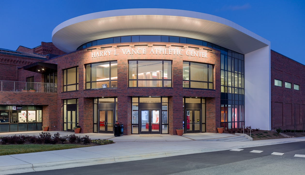 Advantus exterior lighting fixtures illuminate a sign on an athletic center at night.