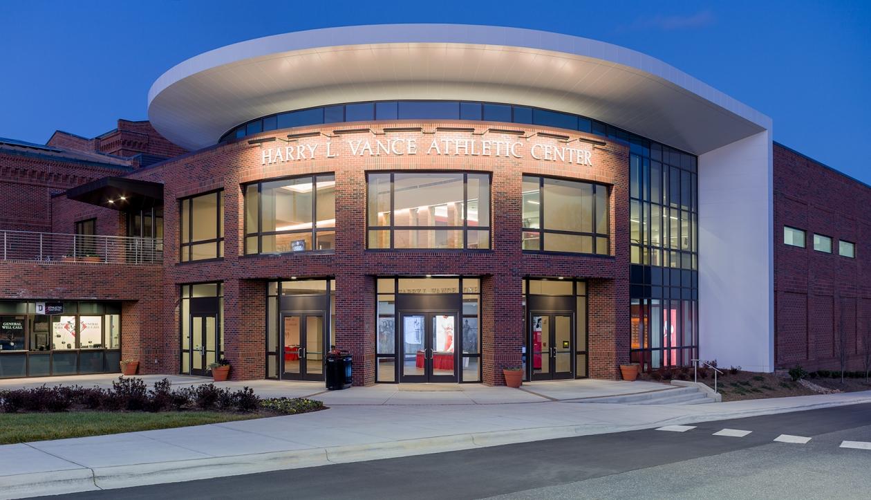 Advantus exterior lighting fixtures illuminate a sign on an athletic center at night.
