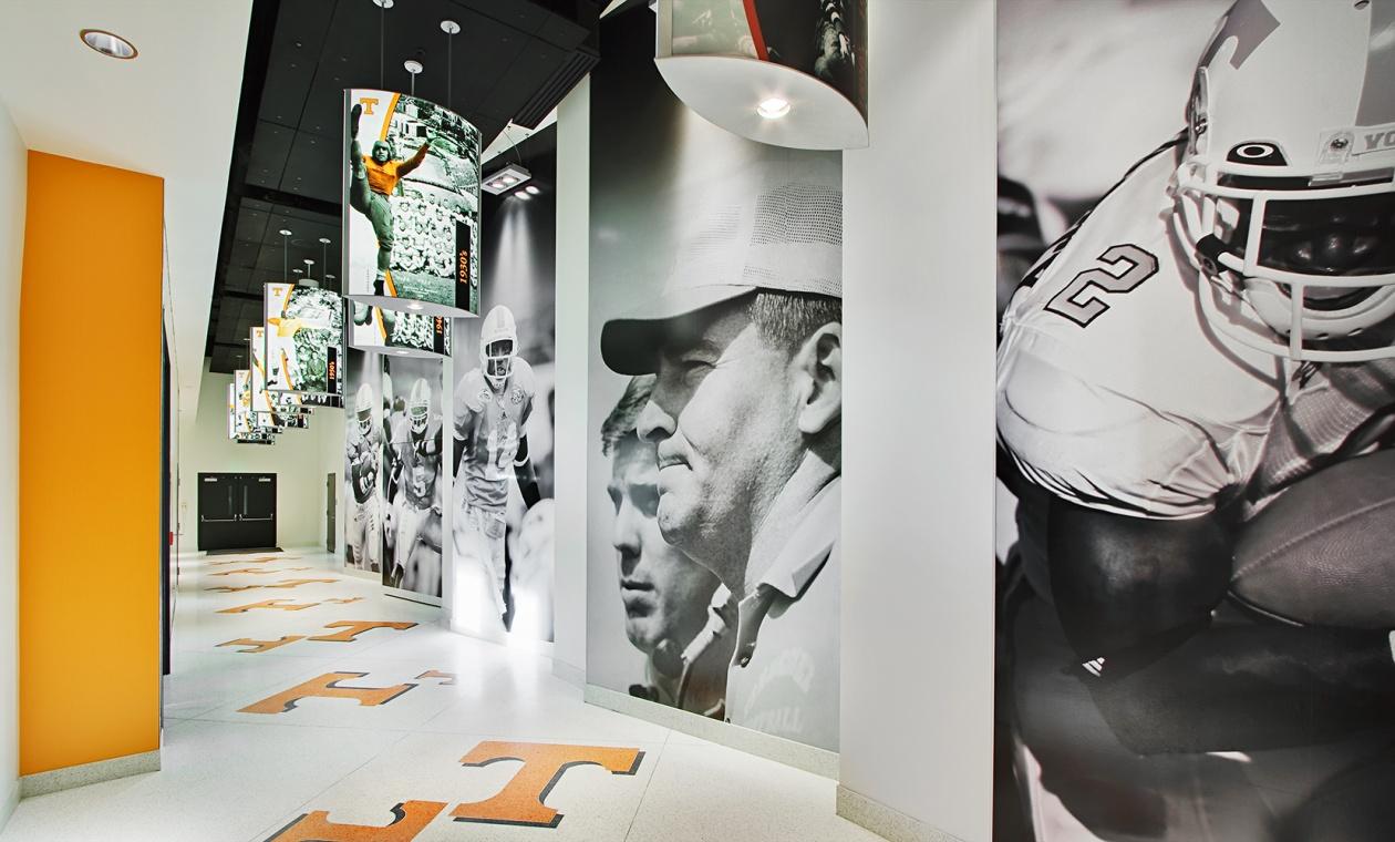 Air Foil custom light fixtures with photograph panels depicting college football players along a stadium hallway.