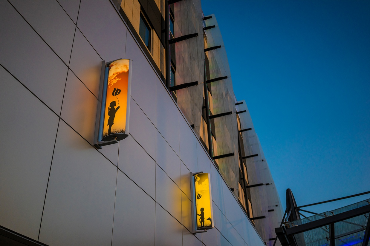 Air Foil custom light fixtures depict artistic silhouette's and deep sunsets as they light a children's hospital façade.