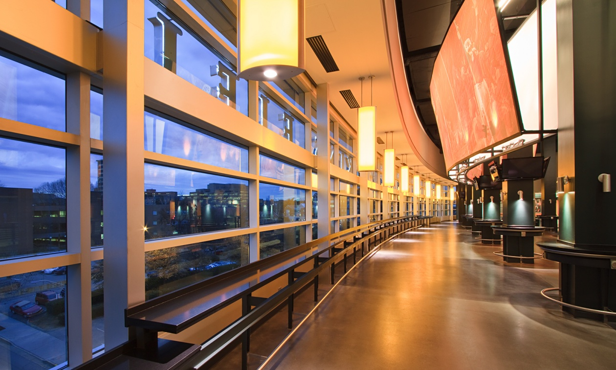 Air Foil education lighting pendants mounted evenly along a curved wall in a college stadium.