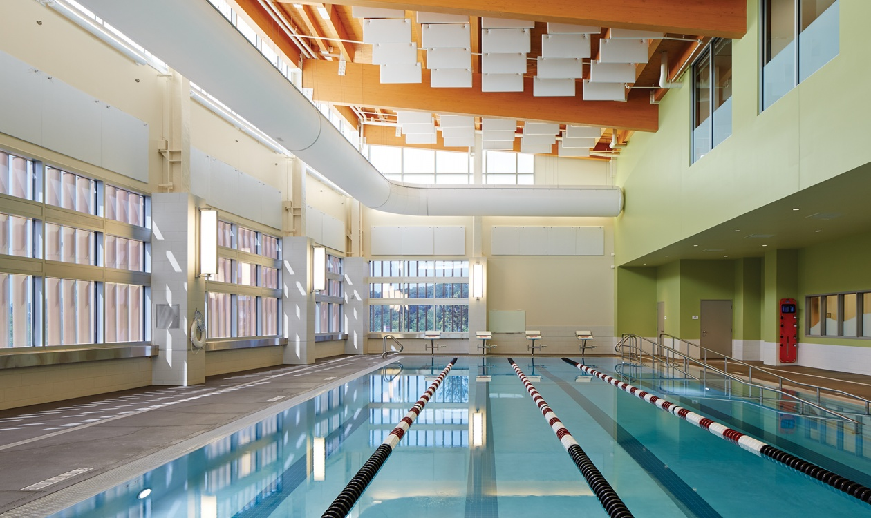 Air Foil sconces showing off modern lighting design along a well-lit indoor pool.