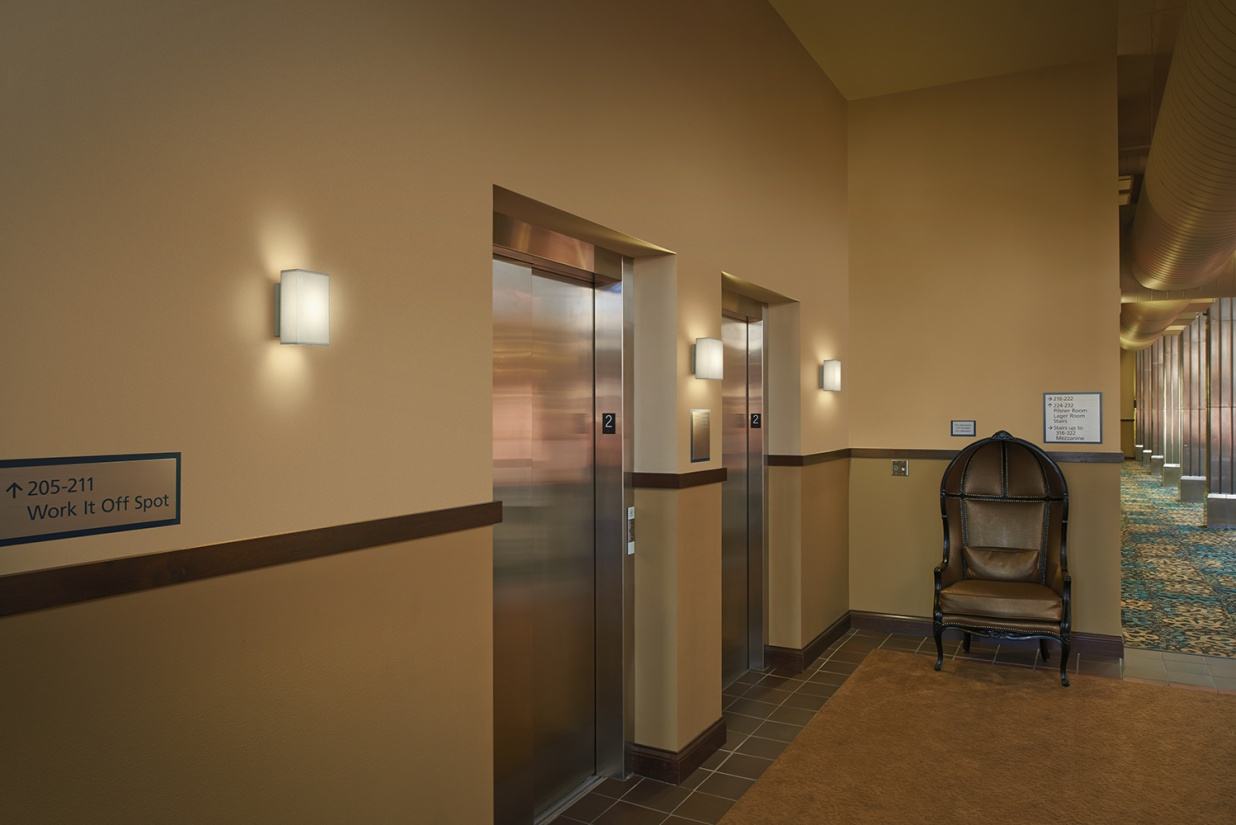 Allegro sconces diffuse soft light alongside hotel elevators, perfect for multifamily design applications.
