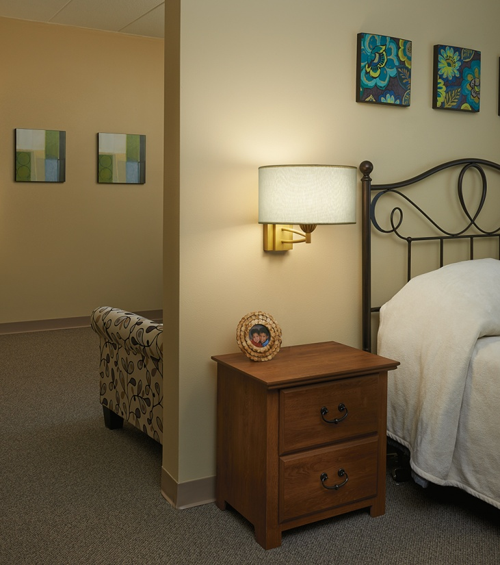 An Allegro wall sconce illuminates a multifamily design bedside.
