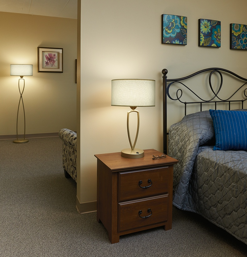 An Allegro portable multifamily design luminaire sits gracefully on a nightstand with a floor lamp in the background.