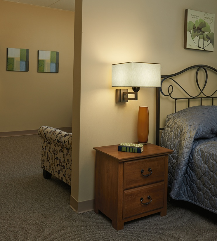 This Allegro wall sconce with a square shade lights a bed and nightstand for a senior living multifamily design aesthetic.
