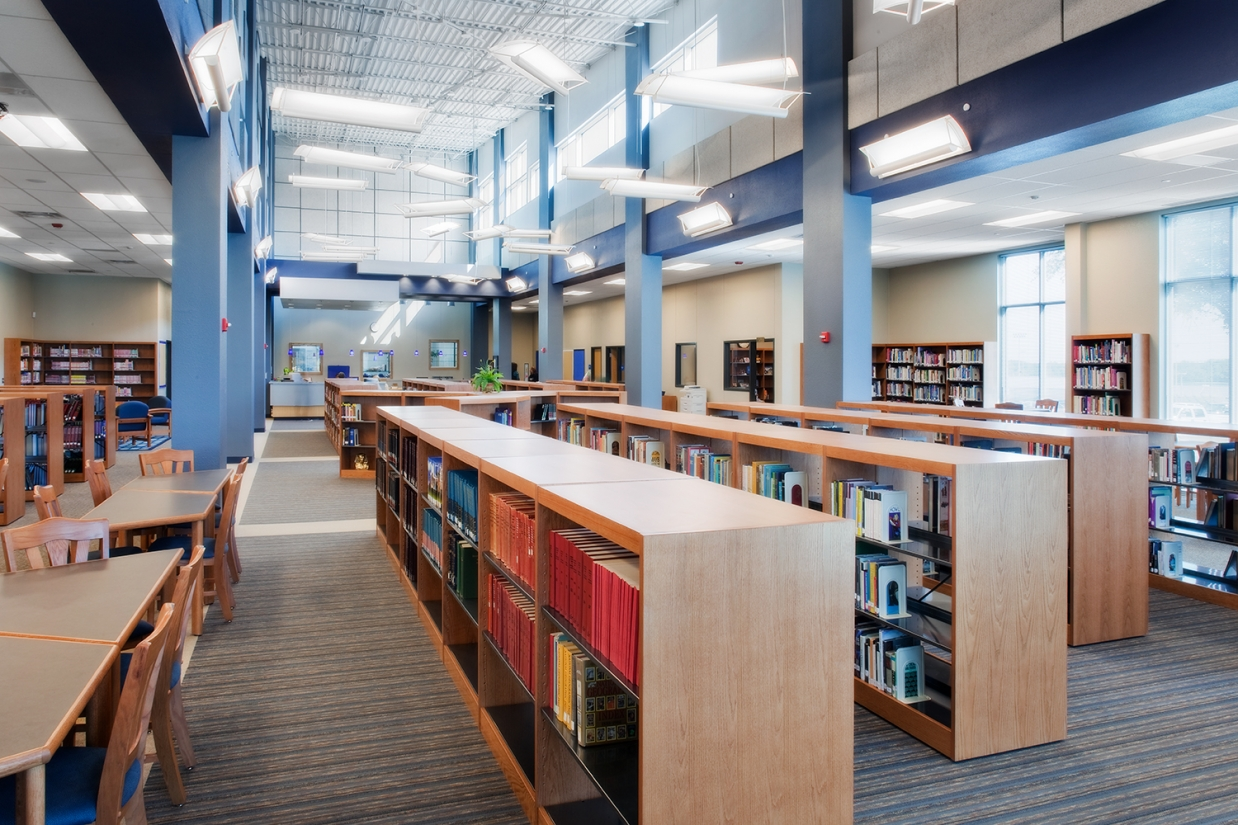 Ascent linear pendants and wall-mounted luminaires illuminate a school library for education lighting design.