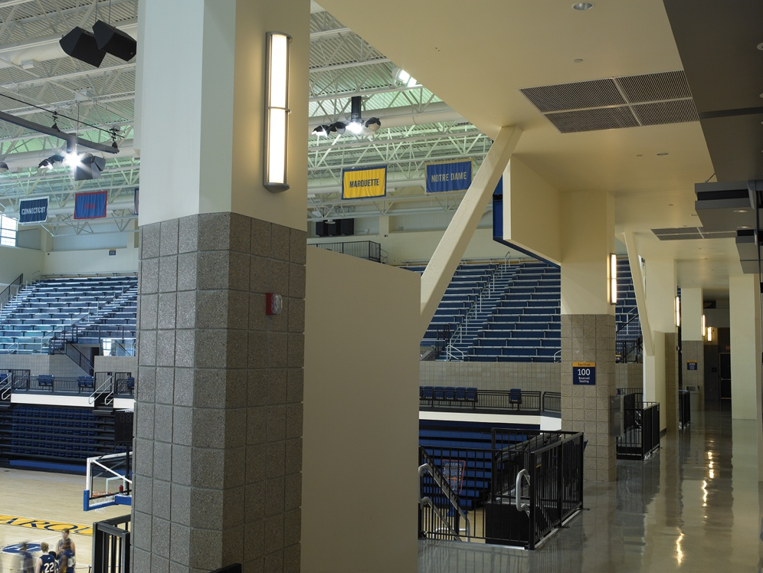 Avatar wall sconces with minimal accent provide modern lighting design for a college basketball gym.