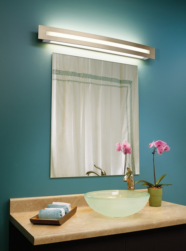 Blush modern vanity light above a simple bathroom mirror and a green wall