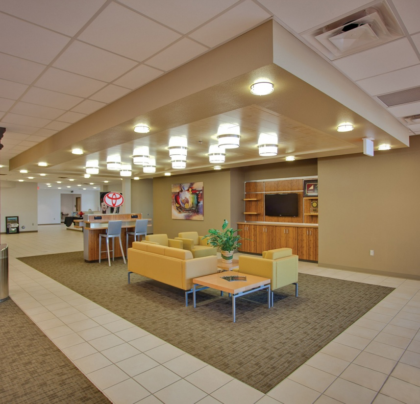 Capitol ceiling-mounted commercial lighting fixtures above a car dealership waiting area.