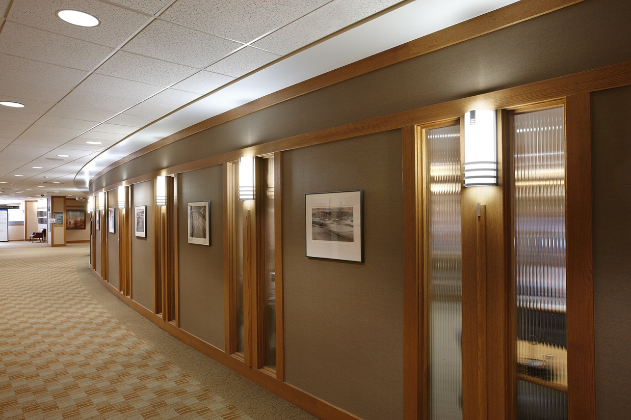 Colonnade wall sconces are classic office lighting fixtures, seen here along an interior hallway.