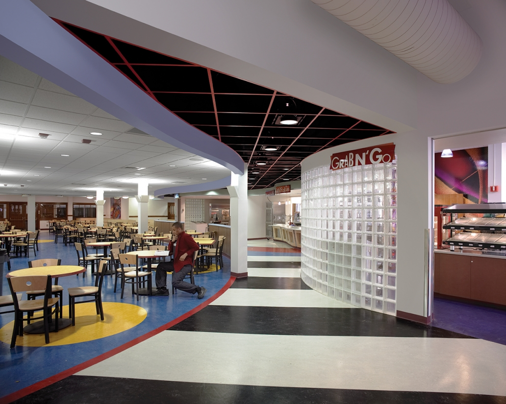 The clean Corona sconce mounted on support columns in a modern education lighting design for a high school cafeteria.
