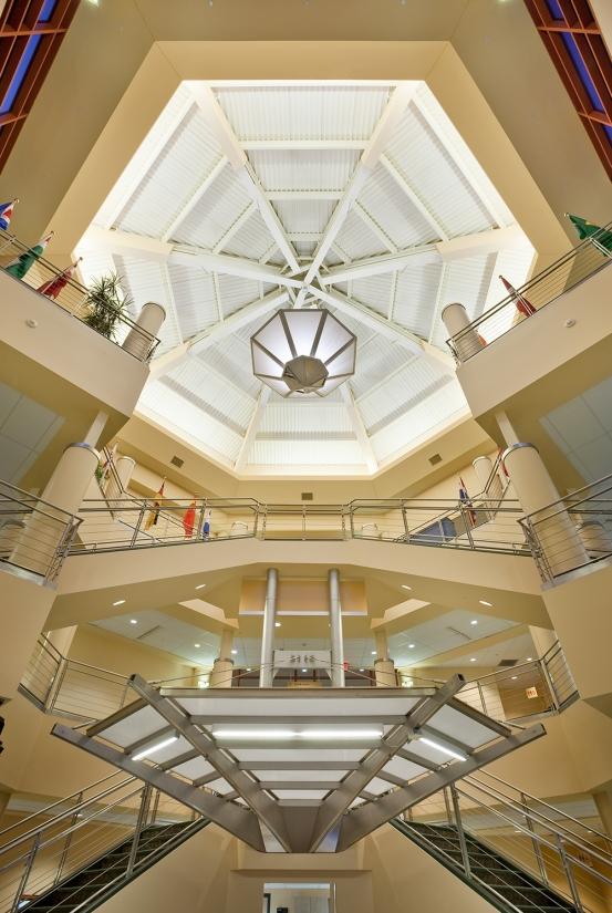 Large, geometric custom light fixtures hang from an open multi-level atrium.