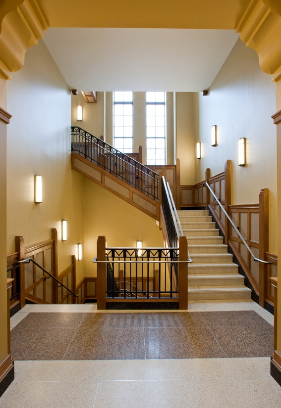 These wall-mounted custom light fixtures illuminate a traditional campus stairwell.