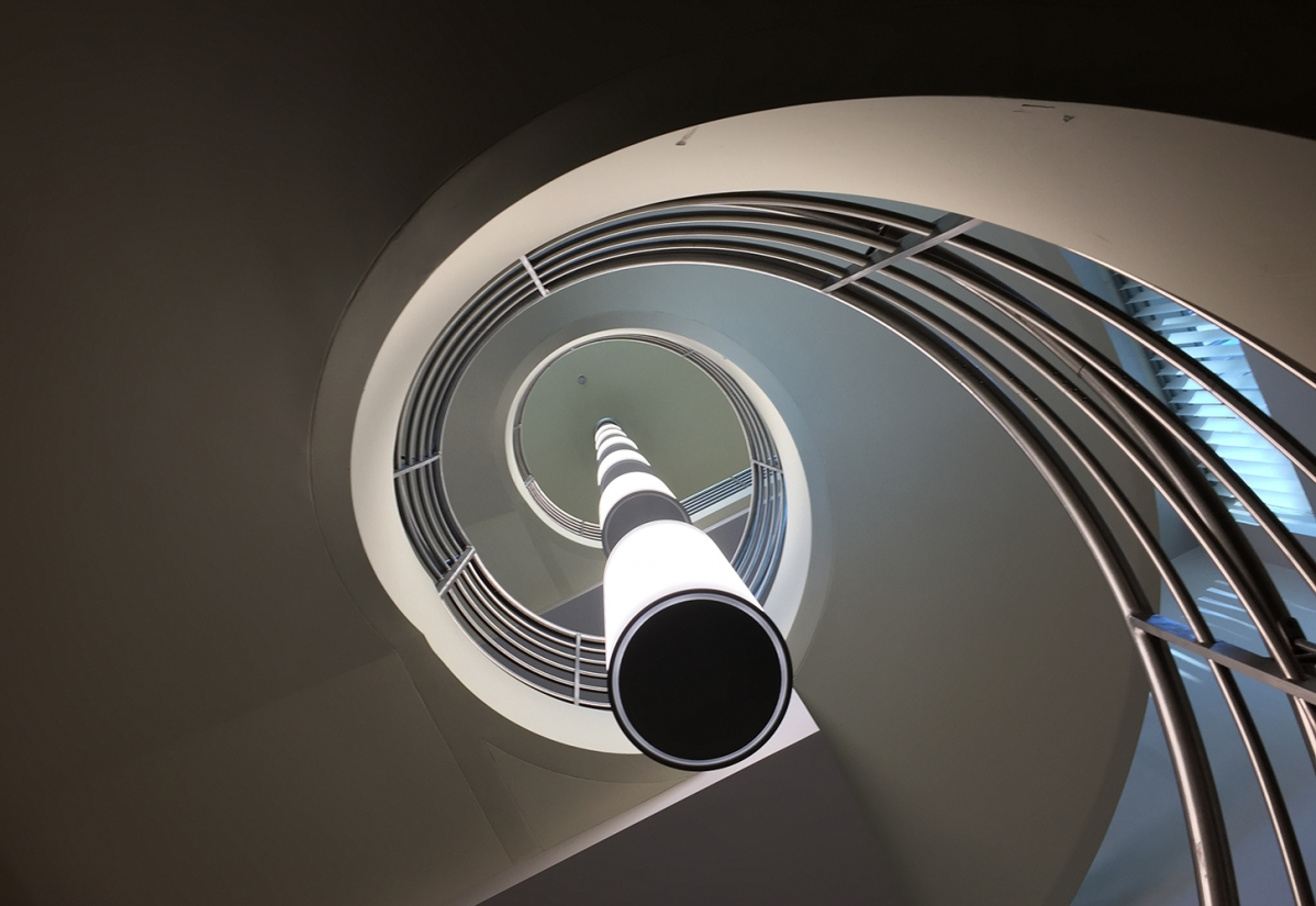 These clean, cylindrical custom light fixtures are hung in tandem down the center of round office stairwell