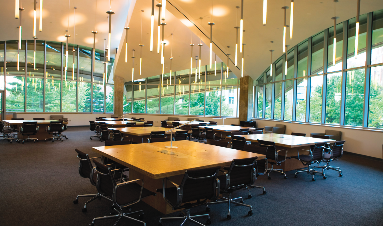 Custom light fixtures in an array of thin luminous tubes brings interest to a large, windowed classroom with group tables.
