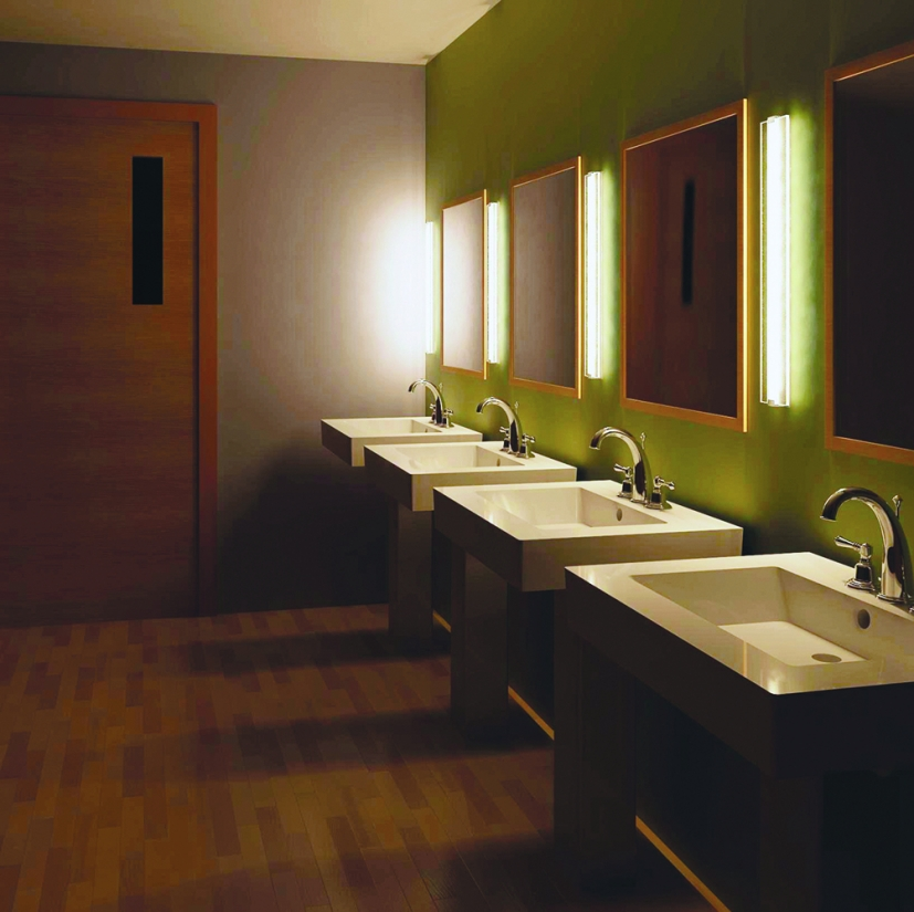 Deck as a modern vanity light fixture, mounted vertically between mirrors in a public restroom