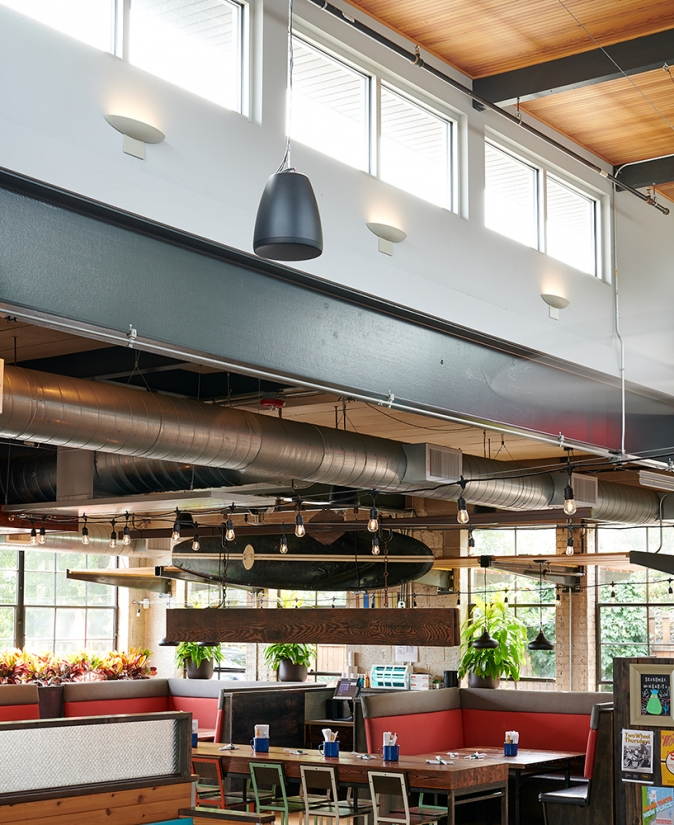 Escape wall sconces are perfect for modern commercial lighting, seen here above a restaurant dining area