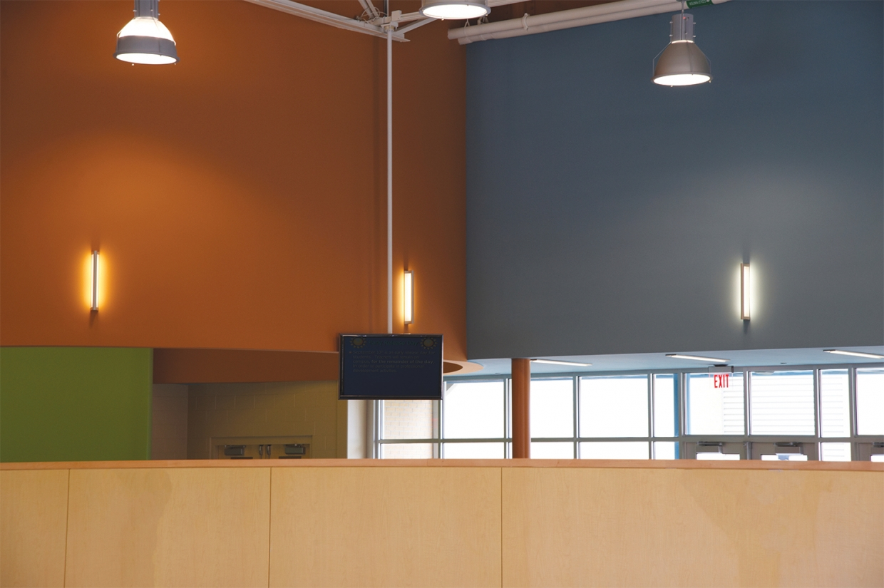 Ether wall-mounted luminaires along colorful classroom walls for a pleasing education lighting design.