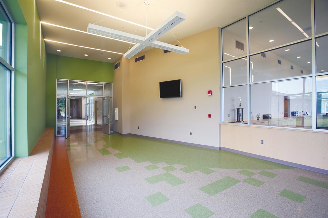 Infinity Performance configurable pendant in educational interior design above school hallway.